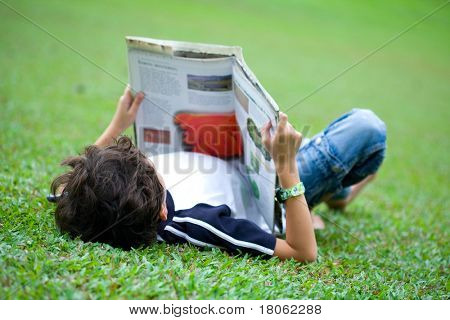 Young boy engross in his reading book in an outdoor park