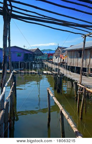 Wooden boardwalk leading to zinc and thatched roof homes of a water's village in Tuaran, Sabah Malaysia.
