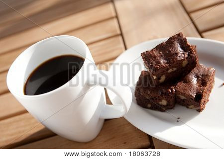 Cup of black coffee with chocolate brownie on side.