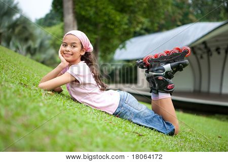 Beautiful young girl resting after rollerblading in the park