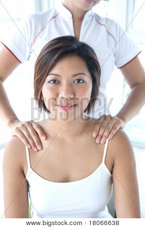 Young Asian woman receiving a shoulder massage by therapist