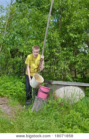 The boy the teenager pours water in a bucket from a well