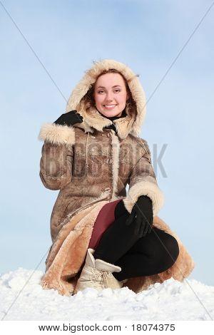 Jovem mulher agachada na mão de capa de neve e porões
