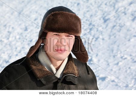 Young man stands in ear-flaps hat in winter and concentrated looks ahead