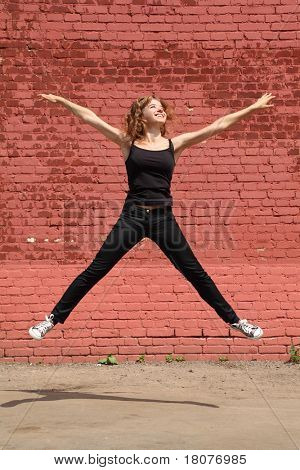 Girl in black clothes jumps with open legs and hands on background of brick wall