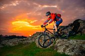 Cyclist Riding the Mountain Bike Down Spring Rocky Hill at Beautiful Sunset. Extreme Sports and Adve poster