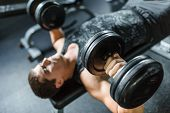High angle view portrait of muscular man doing bench press exercise for chest muscles using heavy du poster