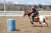 pic of barrel racing  - A young teenage girl turns around a barrel and races to the finish line - JPG
