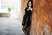 Young Goth Girl On Black Leather Skirt And Jacket Against Grunge Wall. poster