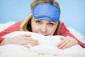 Young Woman Wearing Sleeping Eye Band In Bed poster