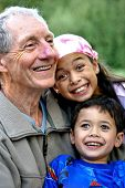 stock photo of priceless  - A young boy and his sister enjoying special times spent with their grandfather - JPG