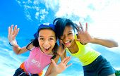 stock photo of summer fun  - Two young girls having fun making funny faces with beautiful sky background - JPG