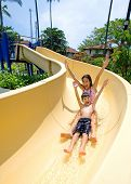 Sister and brother enjoying a fast slide down at tropical swimming pool