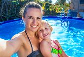 Smiling Mother And Daughter In Swimming Pool Taking Selfie poster