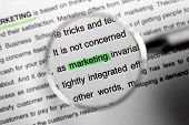 Looking at text with highlighted word MARKETING through magnifier, closeup poster