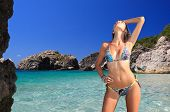 stock photo of bikini model  - Beautiful young woman relaxing on the beach in Greece - JPG