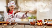 Young chef woman cooker gesturing on copyspace. Raw ingredients served on wooden table, blur modern  poster