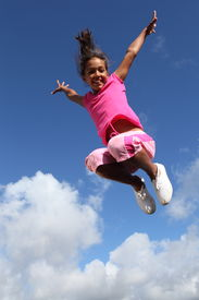 stock photo of ecstacy  - Young school girl jumping for joy against a blue sky with clouds - JPG