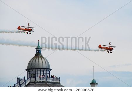 EASTBOURNE, ENGLAND - AUGUST 14: The Breitling wing walking aerobatic display team perform over the Victorian pier at the Airbourne airshow on August 14, 2010 at Eastbourne, East Sussex.