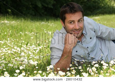 Man resting his chin on his hand, lying in the daisies