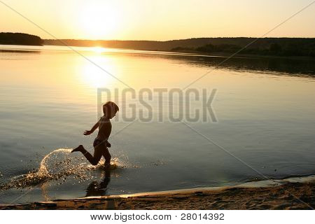 boy running on the evening beach