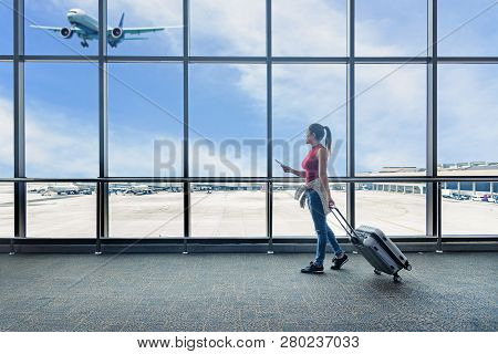 poster of Traveler Women Plan And Backpack See The Airplane At The Airport Glass Window. Asian Tourist Hold Ba