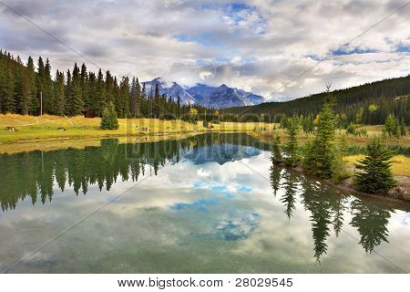 Lake in mountains surrounded by a wood and the cloudy sky above it