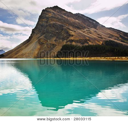 The huge rock of the triangular form is reflected in emerald waters of cold mountain lake