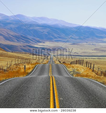 The Californian prairie and mountains in the distance, autumn day. Magnificent American road and fencings