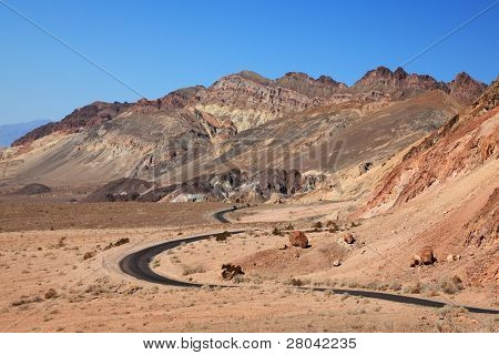 Winding road in Death Valley. Dry clay soil and a cloudless sky