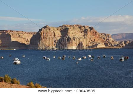 Flotilla of elegant white yachts on Lake Powell. Small waves on the lake from the evening breeze