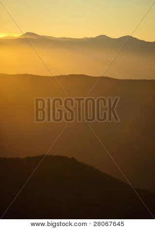 sunrise shining over mountains