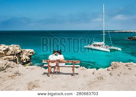 poster of Honeymoon Traveller Couple Hugging On A Wooden Bench And Enjoys Their Tropical Holiday. Wedding Trav