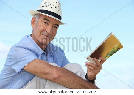Carefree man reading a book outside