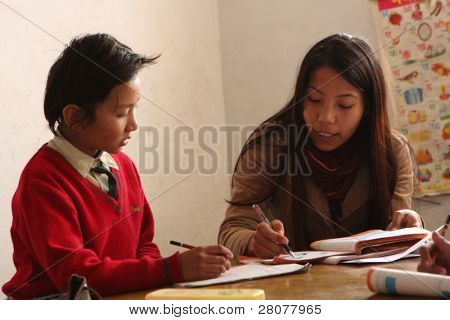 KATHMANDU, NEPAL - JANUARY 1: A teacher conducts lessons in small primary school