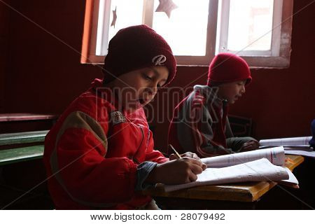 """KATHMANDU, NEPAL - JANUARY 1: Pupil in a learning session during lesson in small primary school """"Happy Home School"""" in poor area of city, January 1, 2009 in Kathmandu, Nepal."""