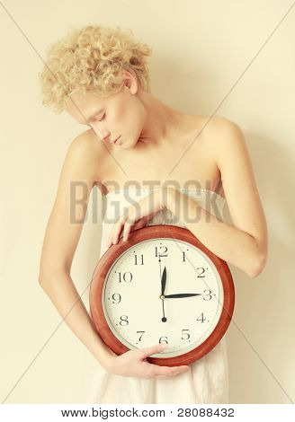 young scrawny woman with big clock in hands