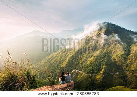 poster of The Couple Greets The Sunrise In The Mountains. Man And Woman In The Mountains. Wedding Travel. The