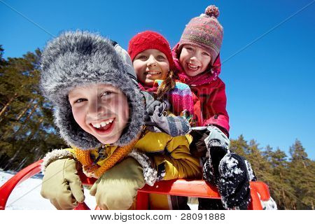Happy friends in winterwear tobogganing in park