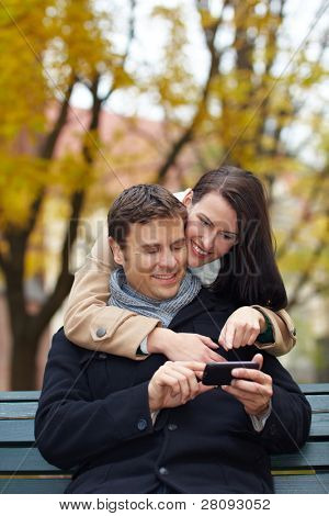 Happy couple on park bench using a smartphone