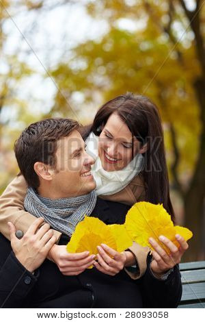 Woman collecting autumn leaves and showing them to man