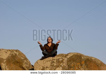 Young man is meditating while sitting on rocks, sunset light
