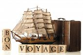 picture of bon voyage  - A brown leather suitcase and model tall ship by rustic alphabet blocks arranged to spell out  - JPG