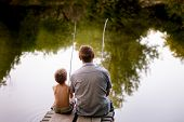 Dad And Son Fishing Outdoors, View From Back. Father And His Son Fishing Together From Wooden Jetty  poster