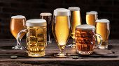 Cold mugs and glasses of beer on the old wooden table at the black background. Assortment of beer. poster