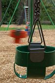 picture of swingset  - Swingset with chairs and one in motion - JPG