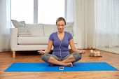 yoga, technology and mindfulness concept - woman with smartphone and earphones meditating in lotus p poster