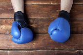 Mens Hands In Boxing Gloves On A Wooden Background. Ready Gesture. The Concept Of Training For Boxin poster