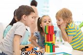 Little Kids Build Wooden Toys At Home Or Daycare. Emotional Kids Playing With Color Blocks. Educatio poster