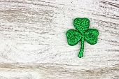 Single St Patricks Day Glittery Shamrock Over An Old Rustic White Wood Background poster
